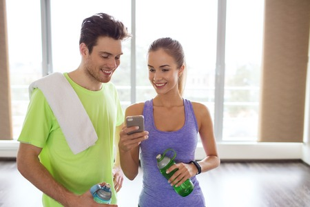 46993391 - fitness, sport, technology and slimming concept - smiling young woman and personal trainer with smartphone and water bottles in gym